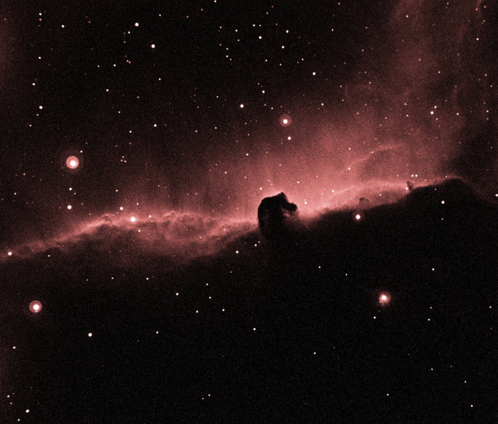 Nebula of red hydrogen gas from the Horsehead nebula surrounded by stars