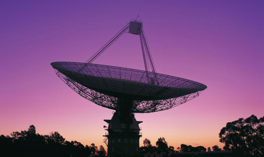 Parkes radio telescope dish facing skyward against a purple sunset sky
