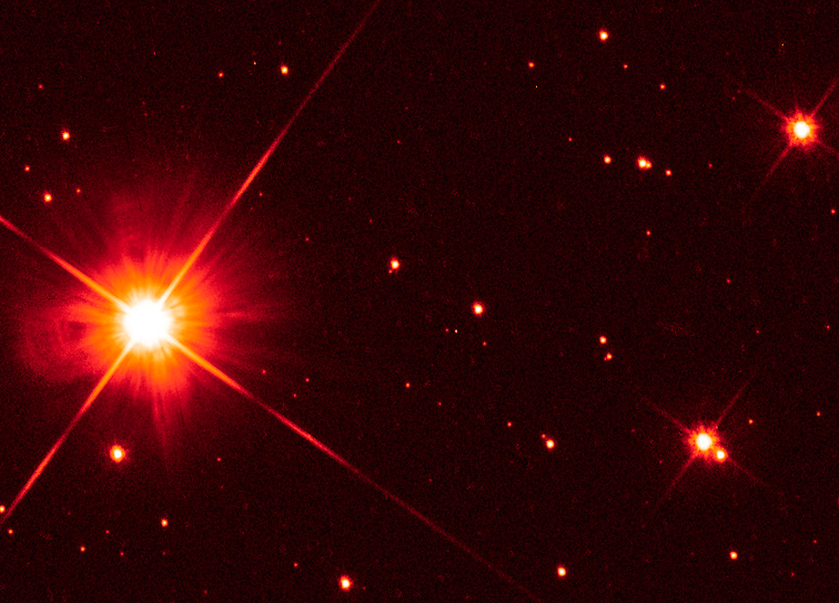 Hubble image of Proxima Centauri with two stars nearby.