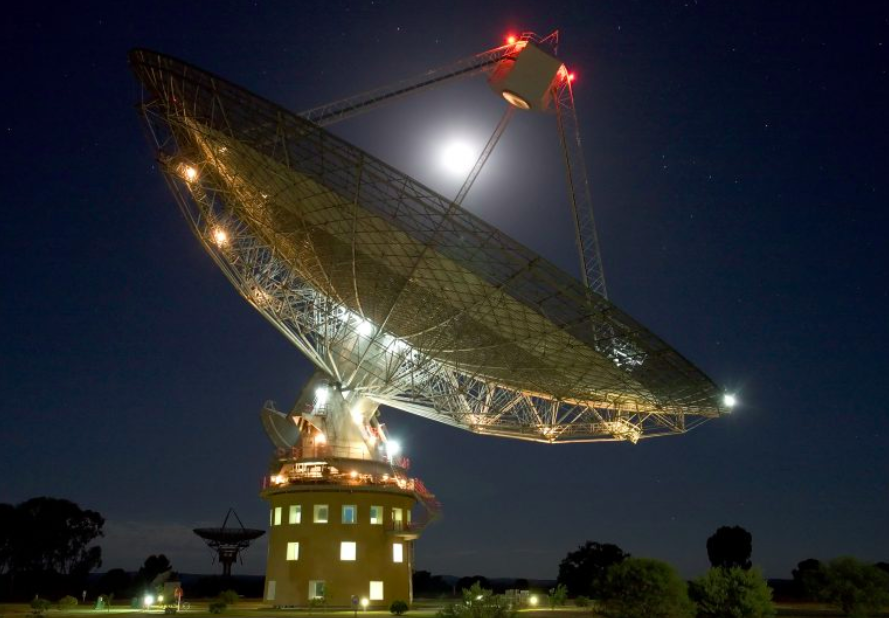 The Parkes Dish photographed at night looking skyward. The bright moon is behind it.