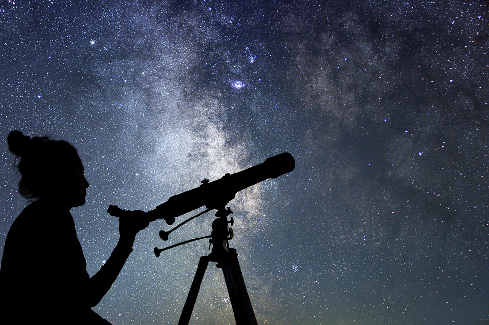 Silouette of woman looking into space holding telescope with milky way band behind her