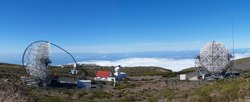 Panoramic image of the twin MAGIC telescopes perched above the mountain top, on each end of the image. In the centre, a lighthouse looking building (control centre) with a red roof. Off in the distance, the clouds are below the telescope altitude indicating a high mountain.