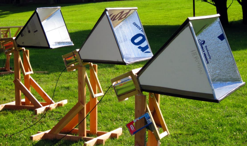 3 home-created horn antennae all lined up on their wooden stands. The antennas are pyramid shaped cones, that connect to a metallic square rectangle at the apex.