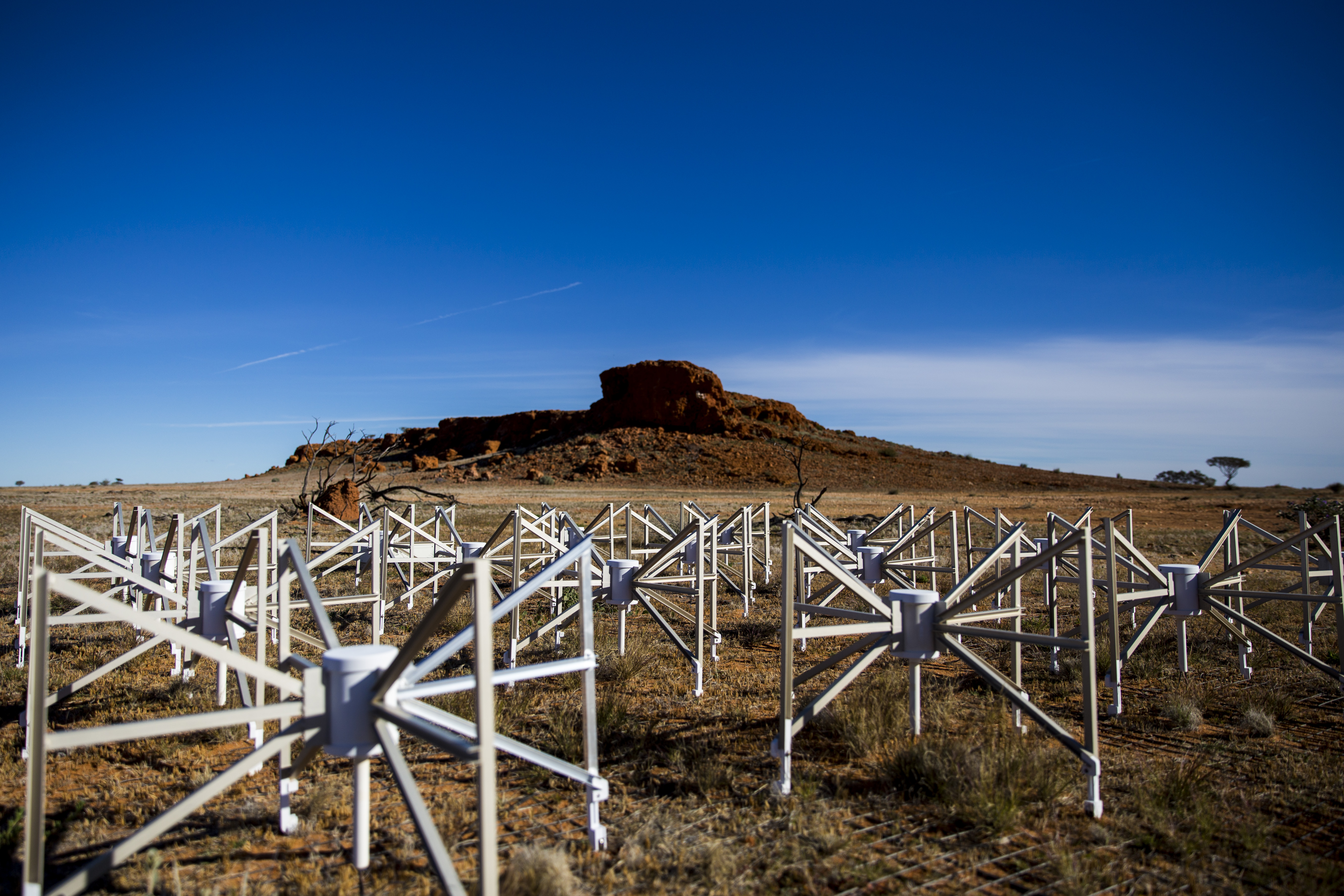 spider-like dipole antennae sitting on mesh in the red desert with a small mountain off in the distance.