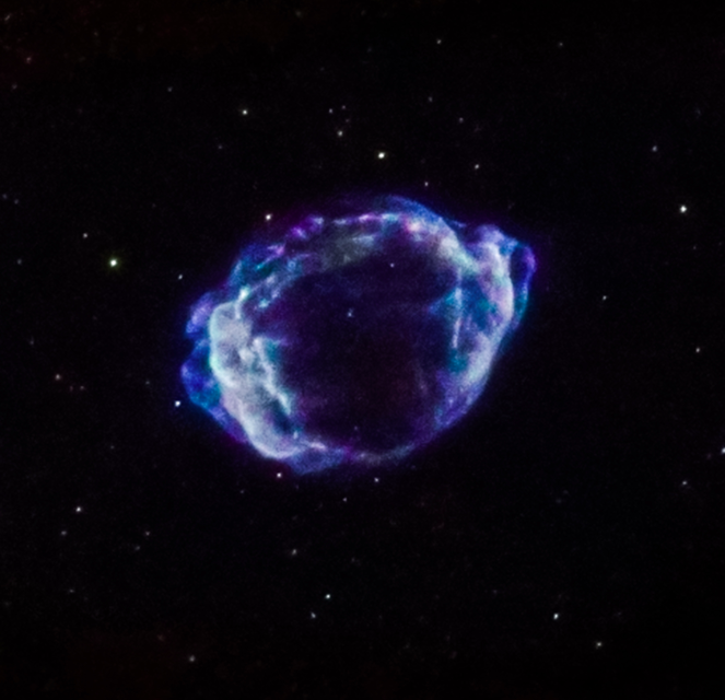 Ring shell structure of bright blue gas, like a circular nebula, set against backdrop of deep space with stars in the background.