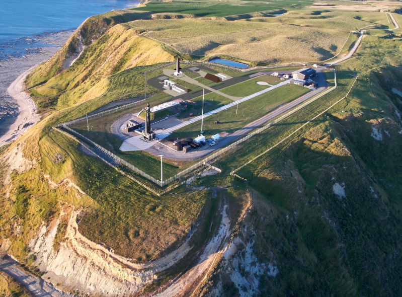 Launch pad facility, perched on top of a cliff and surrounded by green cliffs. Facility contains buildings and long drive out to launch pad which is near end of cliff