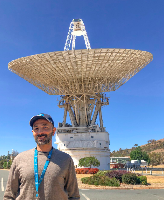 Rami standing in front of the DSN 43 telescope antenna