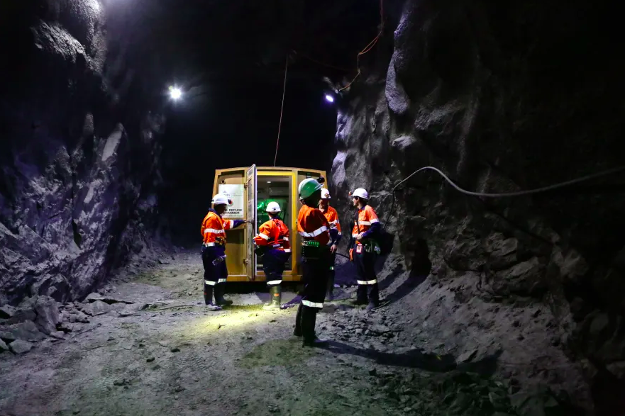 five workers stand inside a dark mine shaft tube. They are standing near a bright yellow vehicle and are all wearing high-viz clothing with helmets and lights on their helmets.