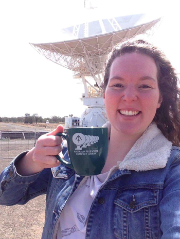 Kat Ross standing with Coffee cup in front of radio telescope