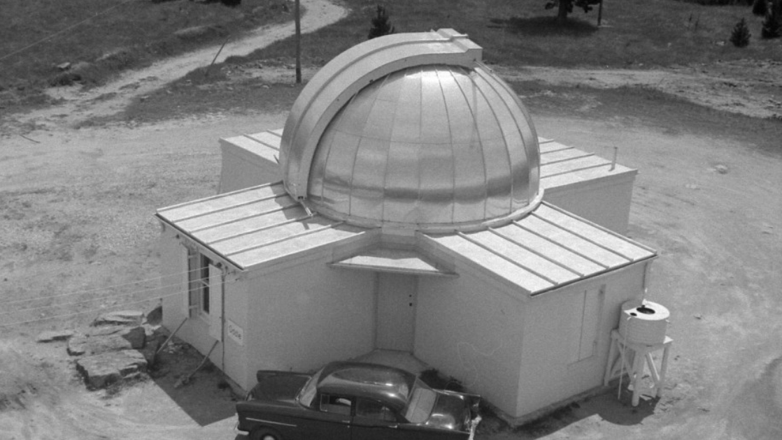 Black and white aerial image of a small observatory dome with a car parked out front. The car is very old fashioned.