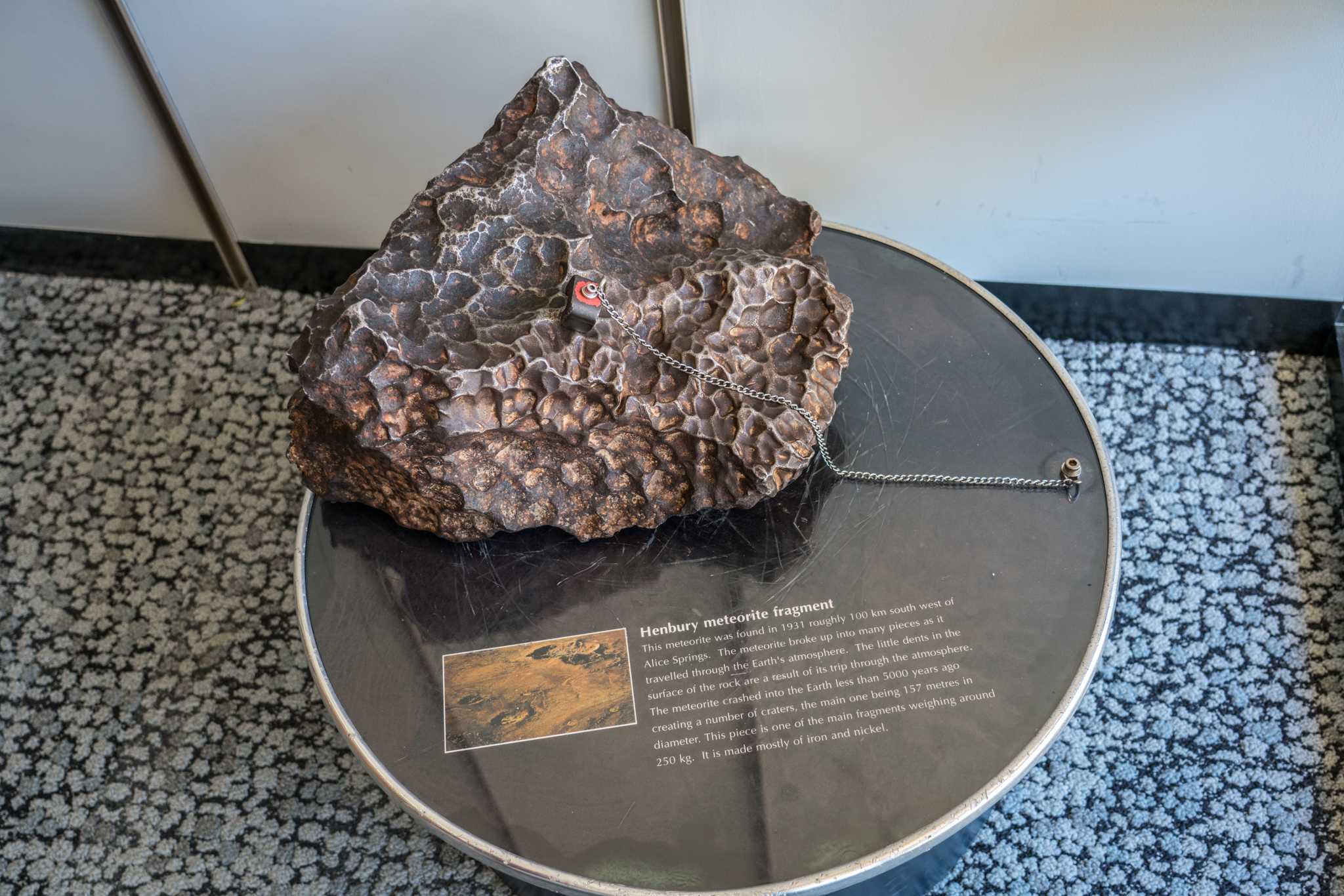 Large meteorite sitting on stand. Meteorite has a chain with magnet attached to it.