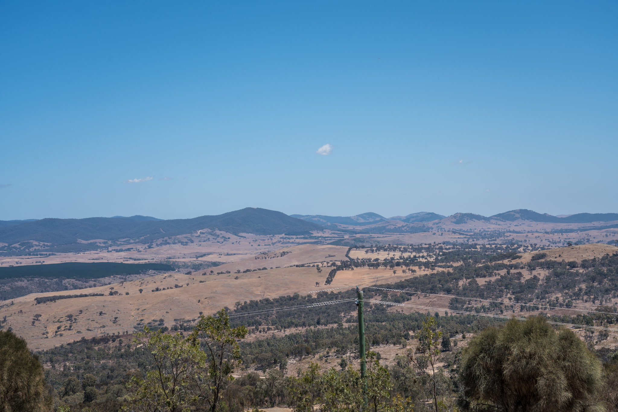Wide-angle shot showing Brindabella mountain ranges off in the distance with open plains leading to us. Ground is dry and pale yellow in colour.