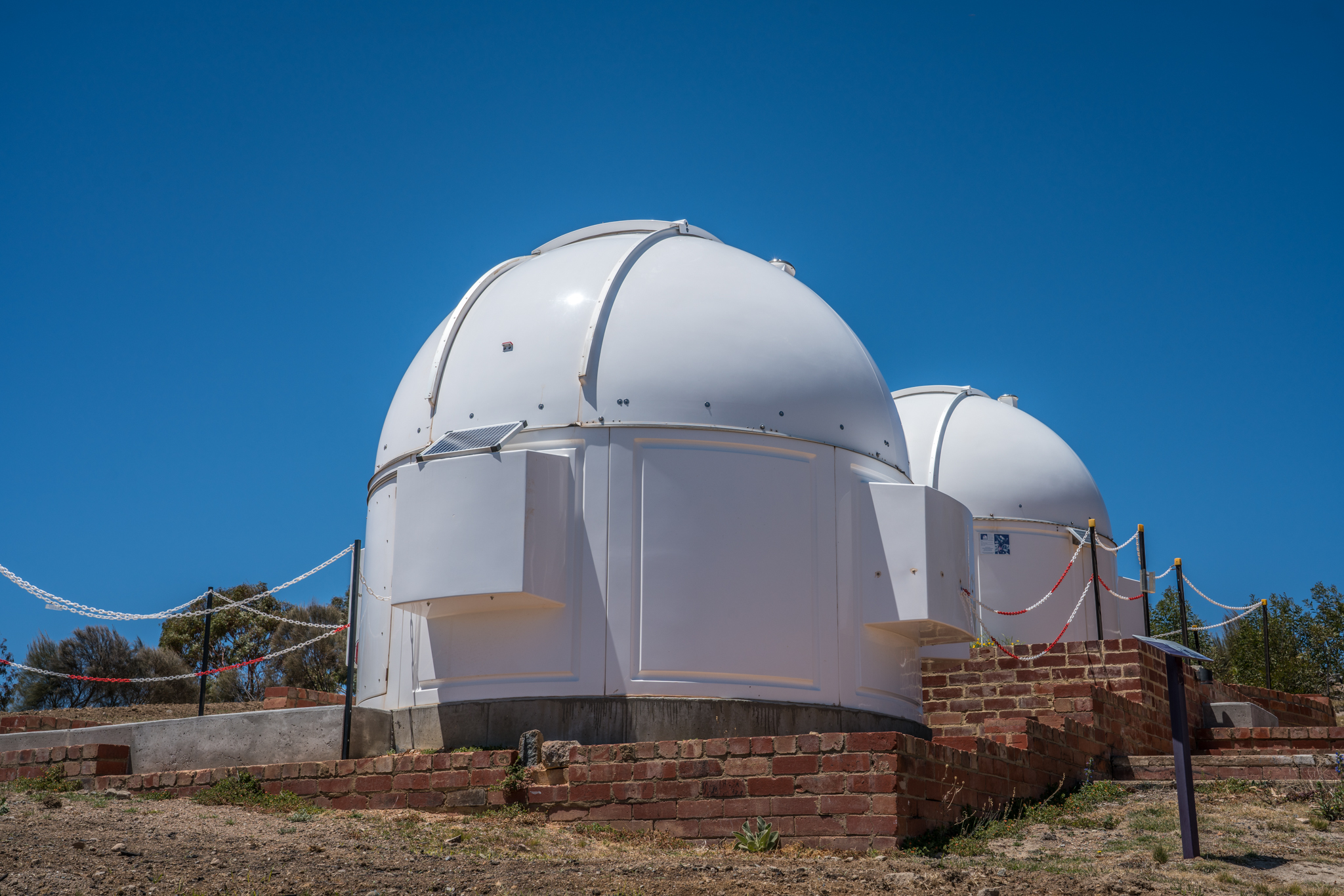 Two small observatory domes, one in front of the other, sitting up a hill on top of the old brick structures.