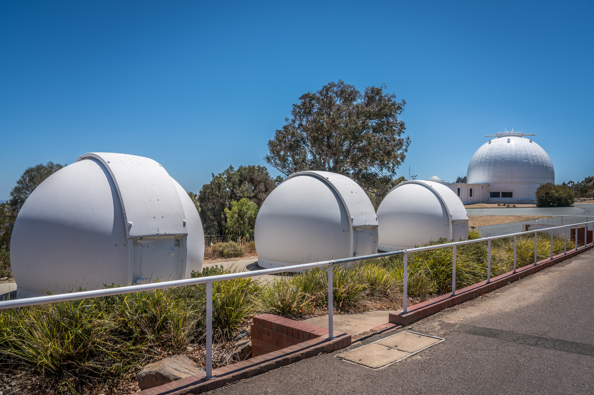 Three small observatory domes are lined up and off in the distance is a larger observatory dome.