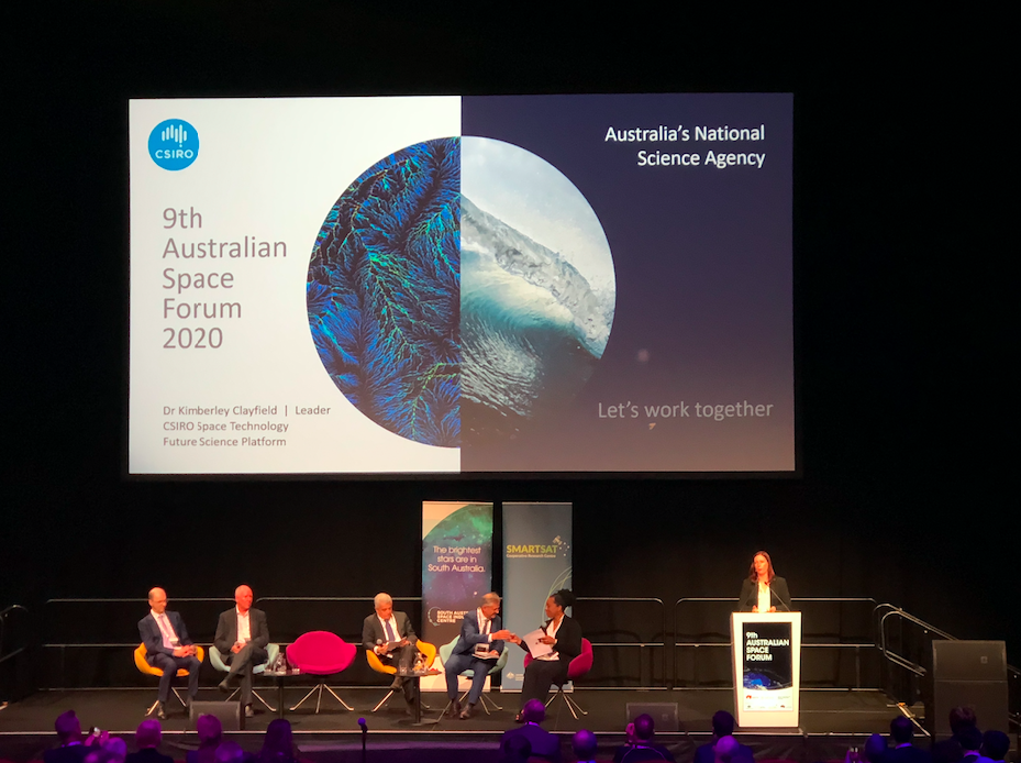 Kimberly Clayfield at lecturn with panel members seated on stage. CSIRO image on screen behind them.