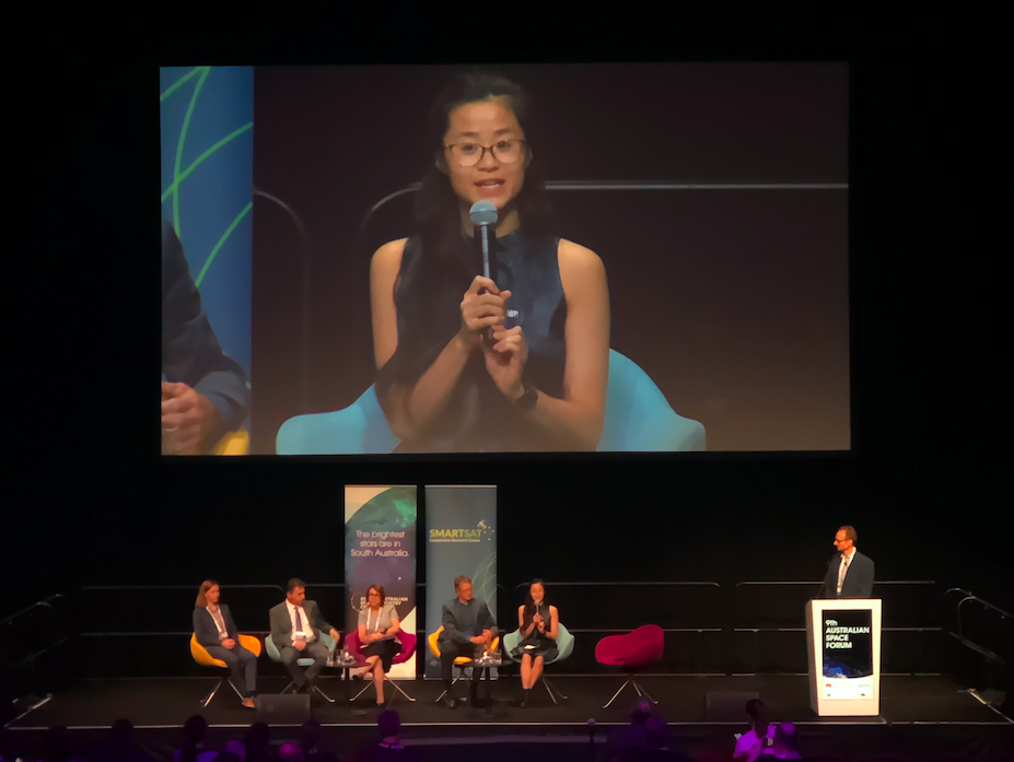 Vi Tran holding a microphone with panel seated around her.