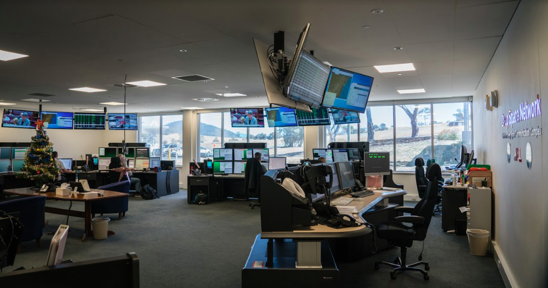 Control room of Canberra DSN showing several workstations, each with several monitors and tv screens hanging from ceiling. In centre of room is a table with a christmas tree wrapped in tinsel.