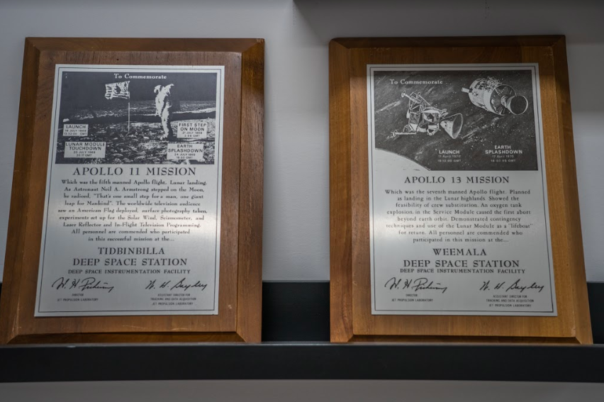 Two plaques up close - Apollo 11 and Apollo 13. Wood frames with metal plates embossed in writing.
