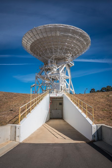 Dish antenna located above a tunnel that leads into an underground room below antenna