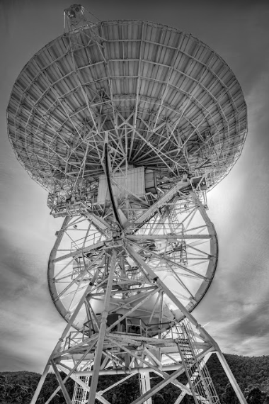 Black and white image of the upper half of the antenna dish, including steel framework mounts and pipes.