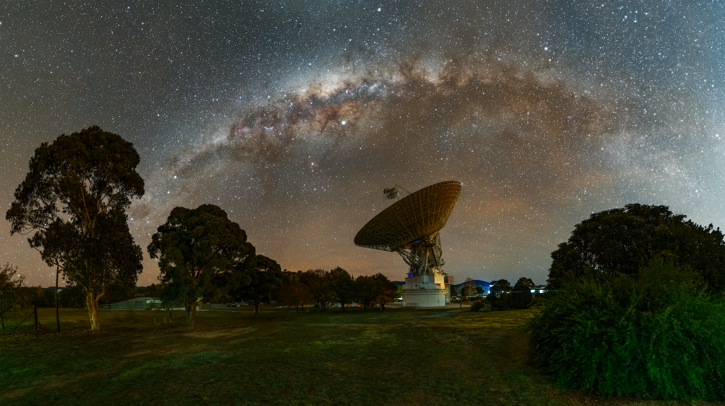 Canberra DSN 43 with milky way arcing over the top wand trees in foreground