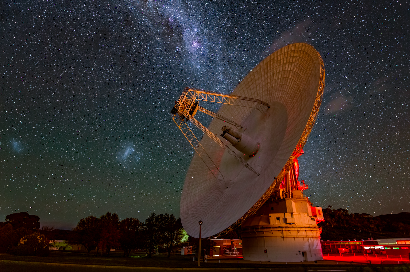 DSS 43 antenna tilted down and illuminated at night, with Milky Way band and smaller galaxies in background.