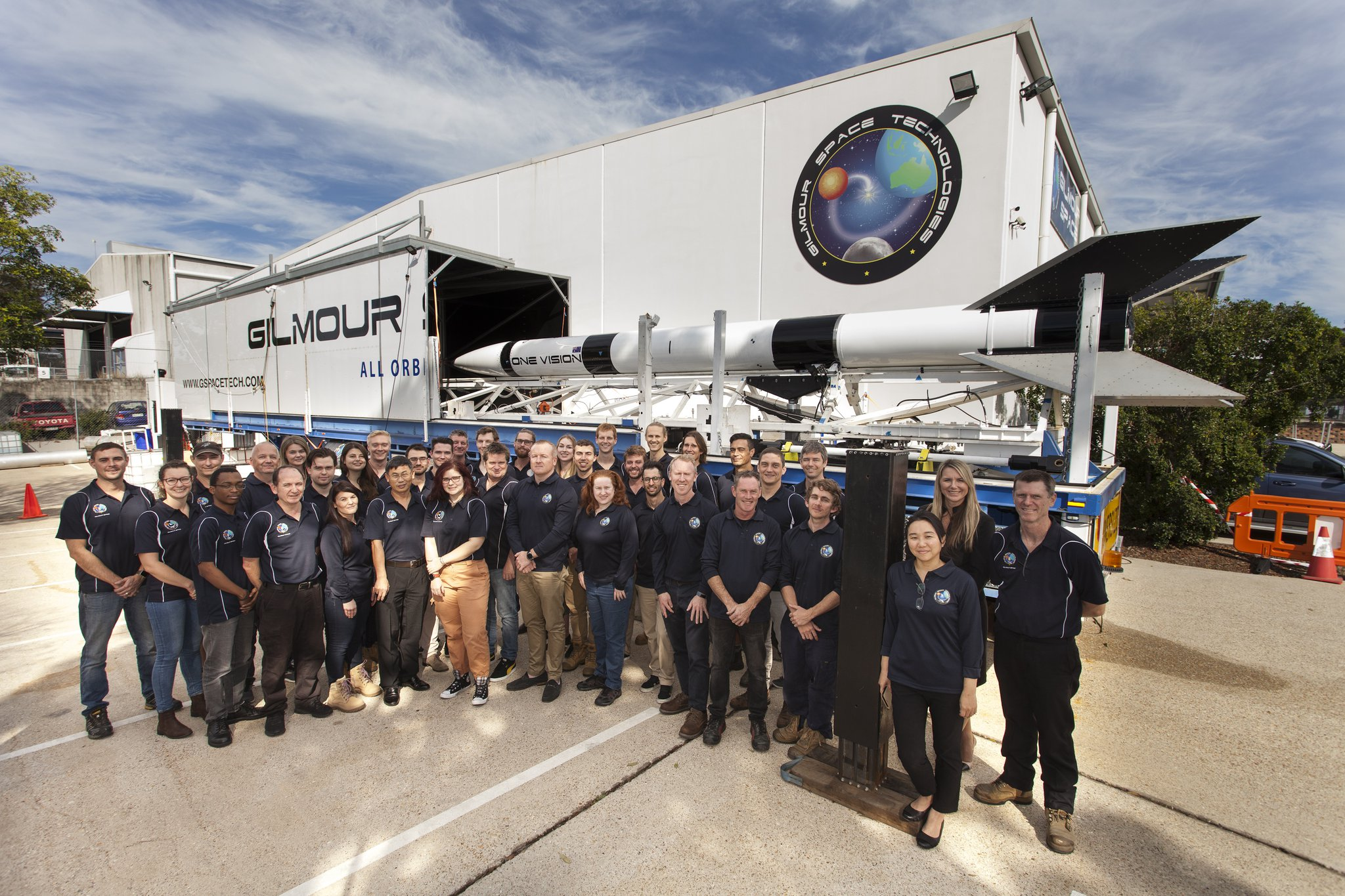 A large group of Gilmour staff members standing in front of a rocket, which is in front of a Gilmour Space building.