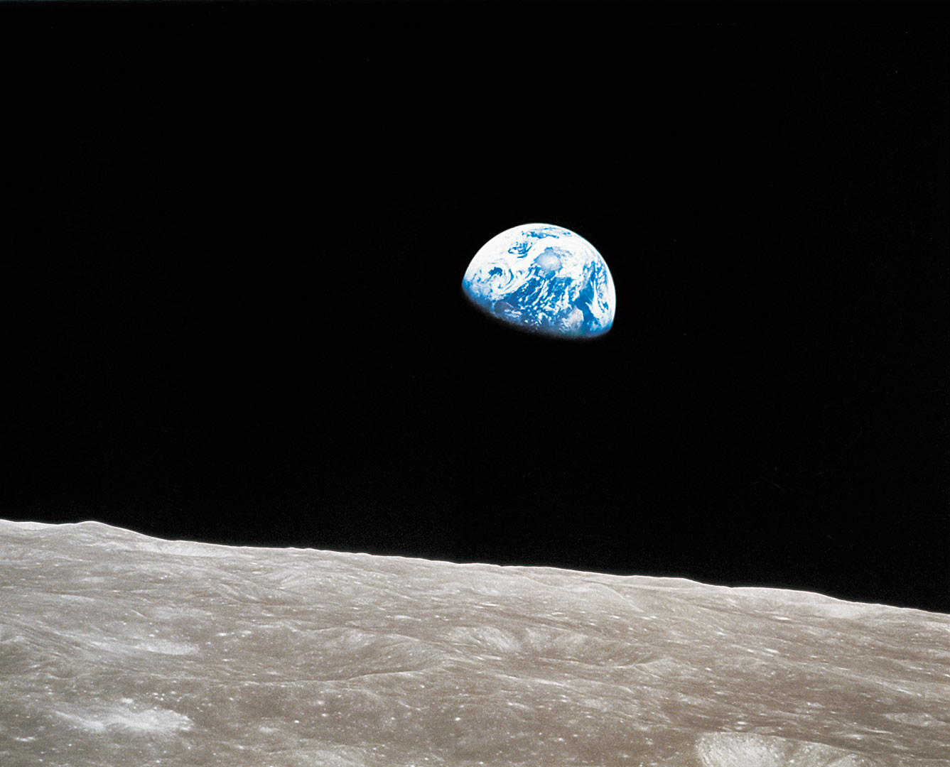 Image of the Earth captured from a lunar spacecraft as it came around the Moon. The Moon is in the foreground and Earth in the background