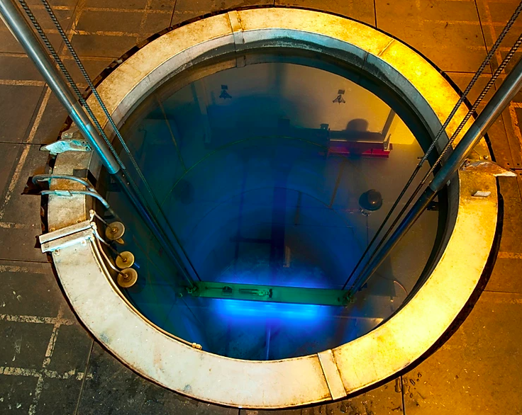 Circular chamber located sub-surface of image showing container with bright blue light emanating from it