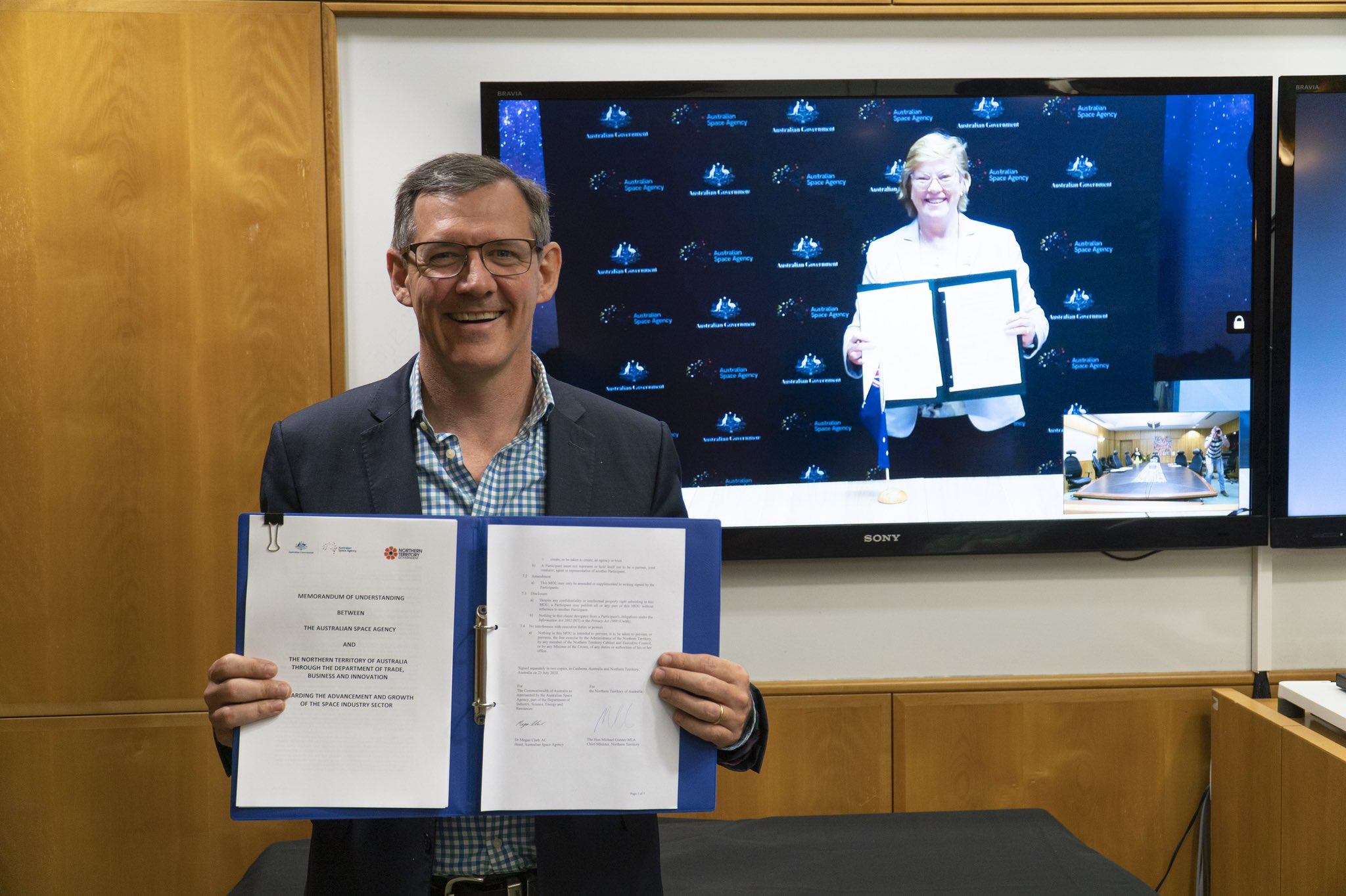 Man standing in foreground holding up open folder showing signature. In background a TV showing a woman also standing up with an open folder showing signature. The image represents both parties signing the MoU through a virtual meeting.