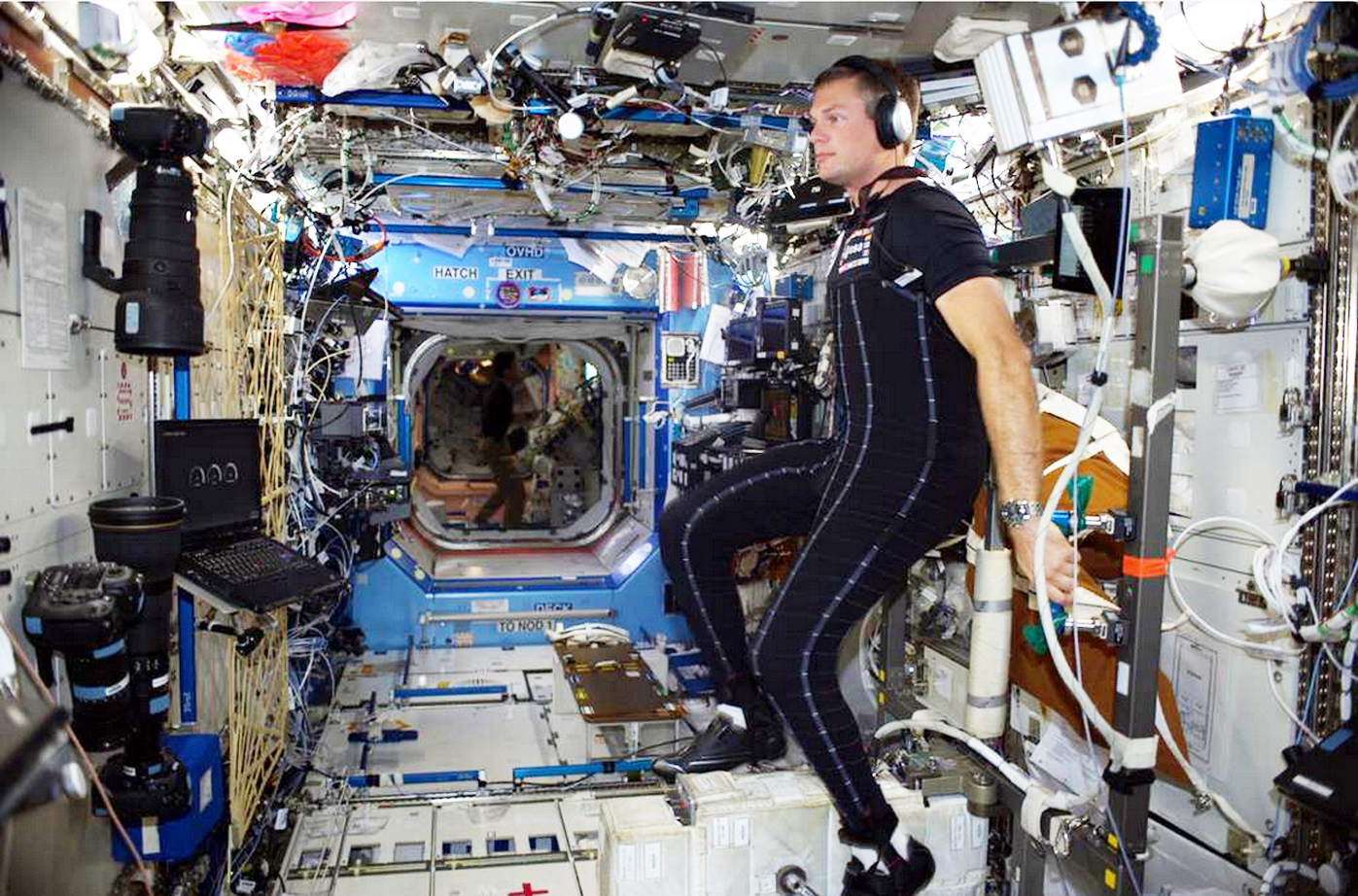 An astronaut wearing skin-tight black clothing is surrounded by lots of different black and white technological devices.
