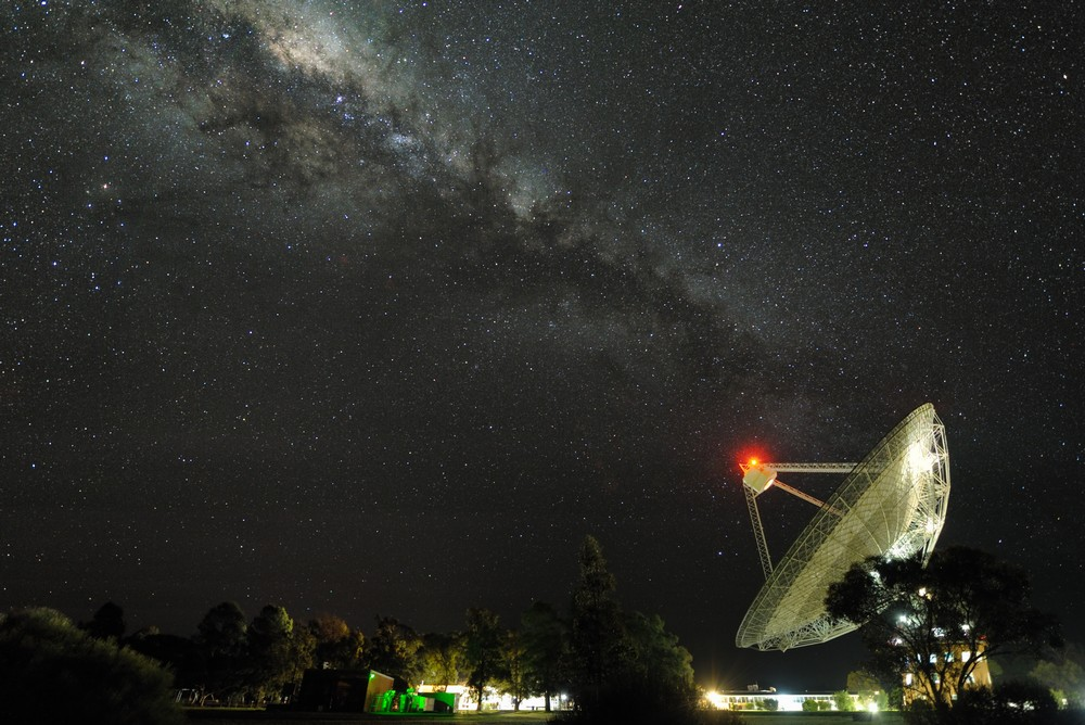Parkes dish captured at night. Dish is illuminated and pointing at 45-degree angle towards top left. The Milky Way band will millions of stars is also rising in that direction.
