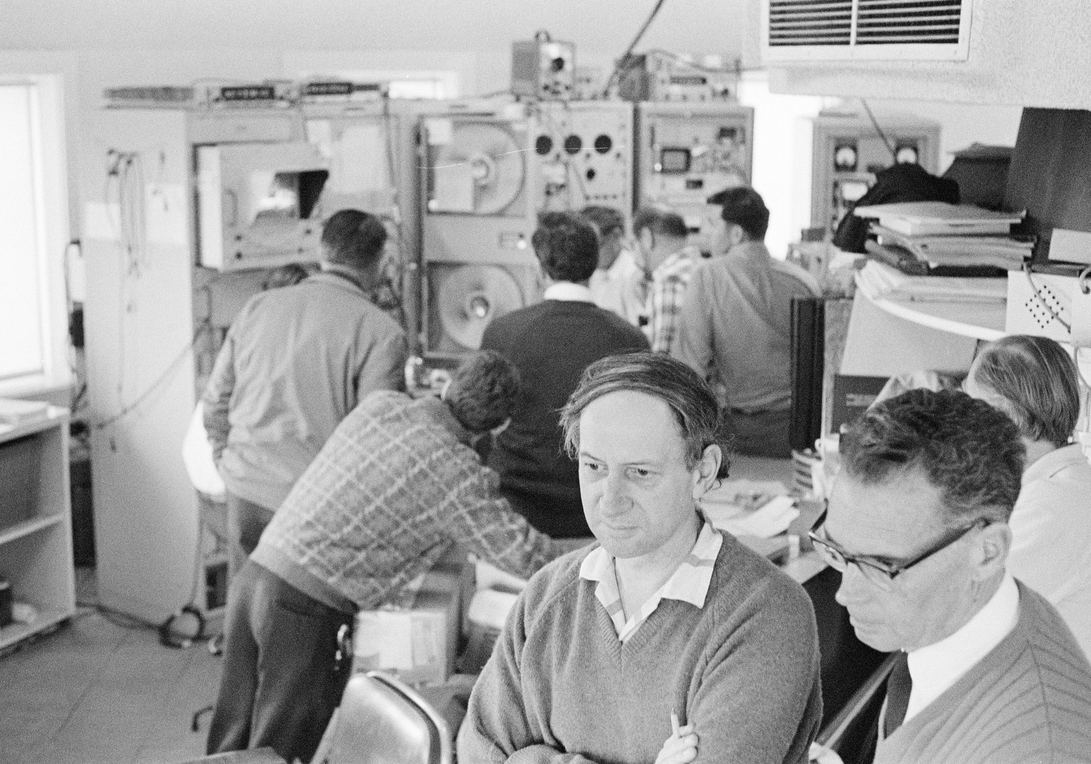 Several men standing around old, large computer gear. Two men in the foreground are looking just off the camera view. One man has his arms crossed. Image is black and white.