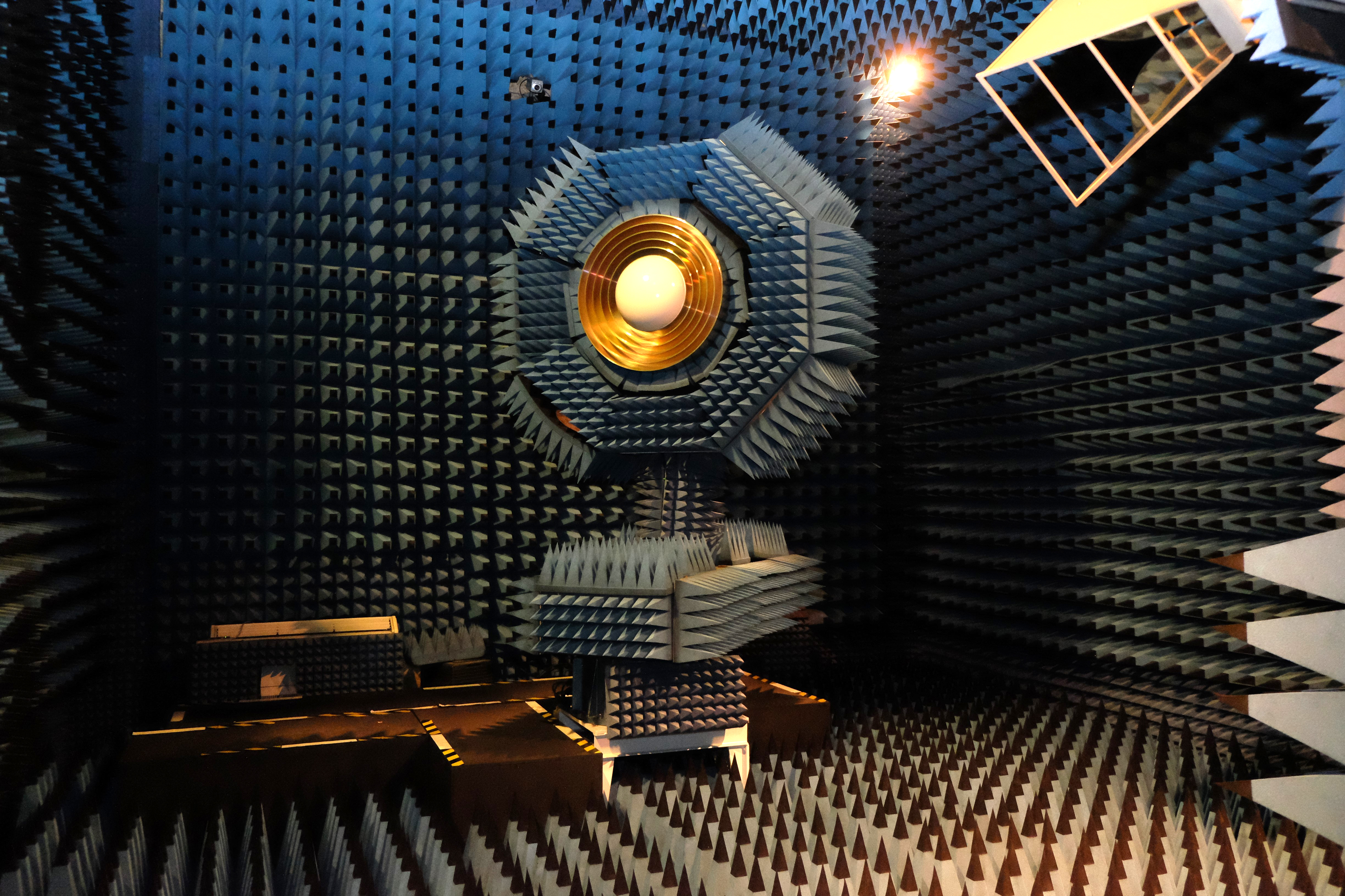 A sound proof room that is covered in small pyramids and spikes made from foam. At the focus is the UWL receiver, a semi circle surrounded by gold concentric rings.