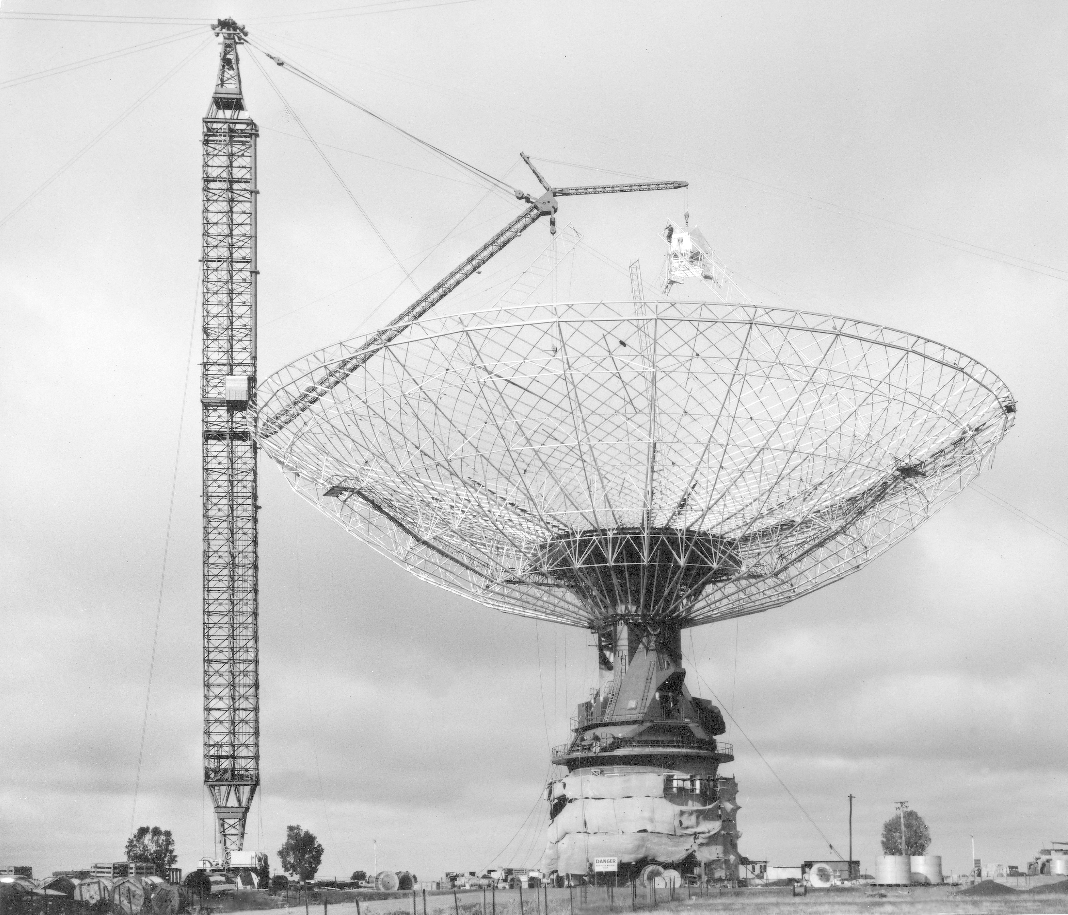 The skeleton of the large telescope being built with the usage of a crane, Image is black and white.