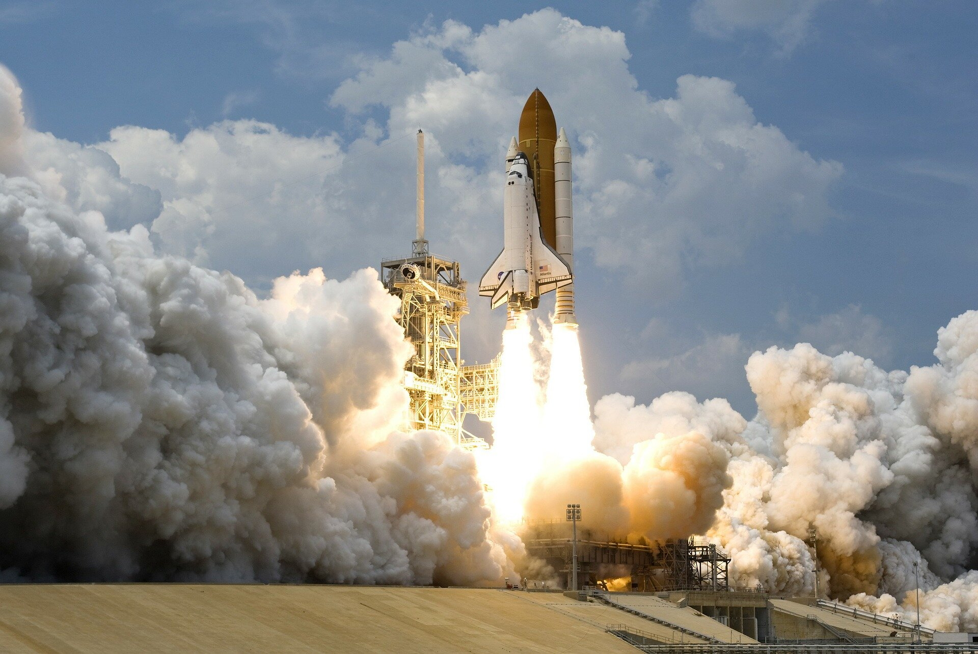 Space Shuttle Atlantis launching from the pad. Bright yellow flames coming out of rocket with big clouds of smoke as shuttle lifts off.
