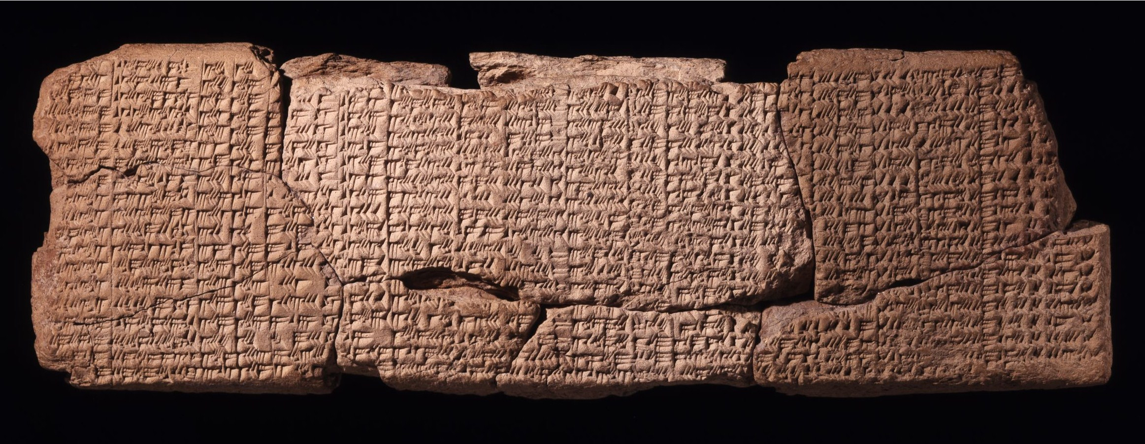 landscape image of several ancient clay tablets which are covered in Babylonian cuneiform writing