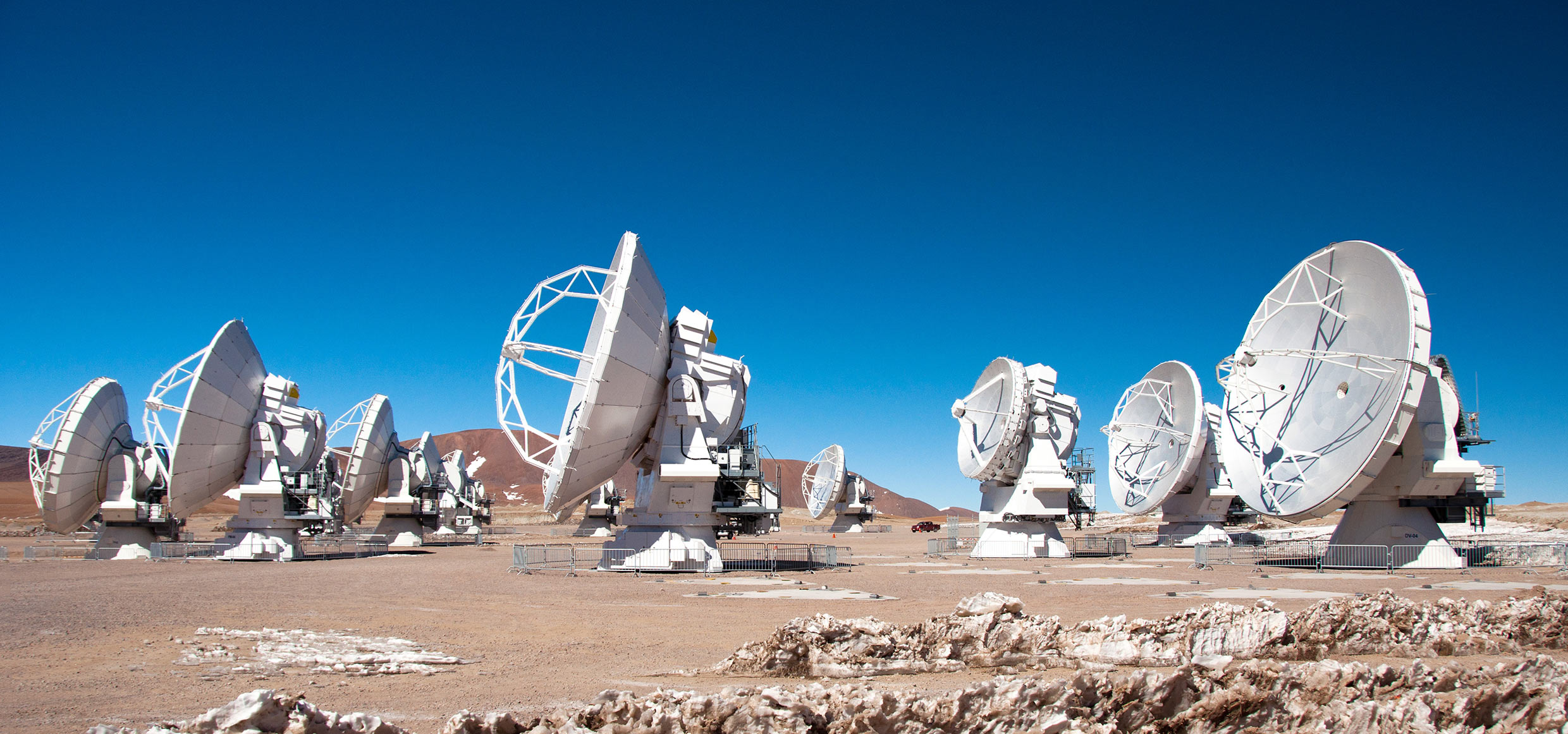 Several radio telescope dishes all pointed towards the left, standing on pale Earth and against a blue sky