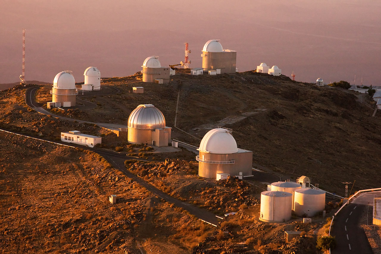 barren rocky Mountain top, bathed in setting orange sunset light, hosting 10 white telescope domes