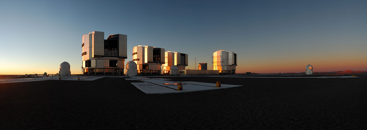 Landscape image of the four VLT housing units taken in sunset light, with sky behind them hues of blue and purple.