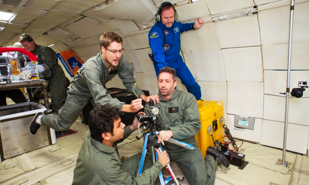 Four people are floating in a zero-gravity environment in blue and green jumpsuits. They are inside a plane, and are gathered around a divide mounted on a tripod.