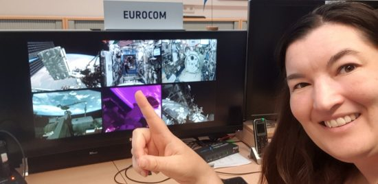 Andrea Boyd at her EuroCom desk pointing to the Astrobee on ISS