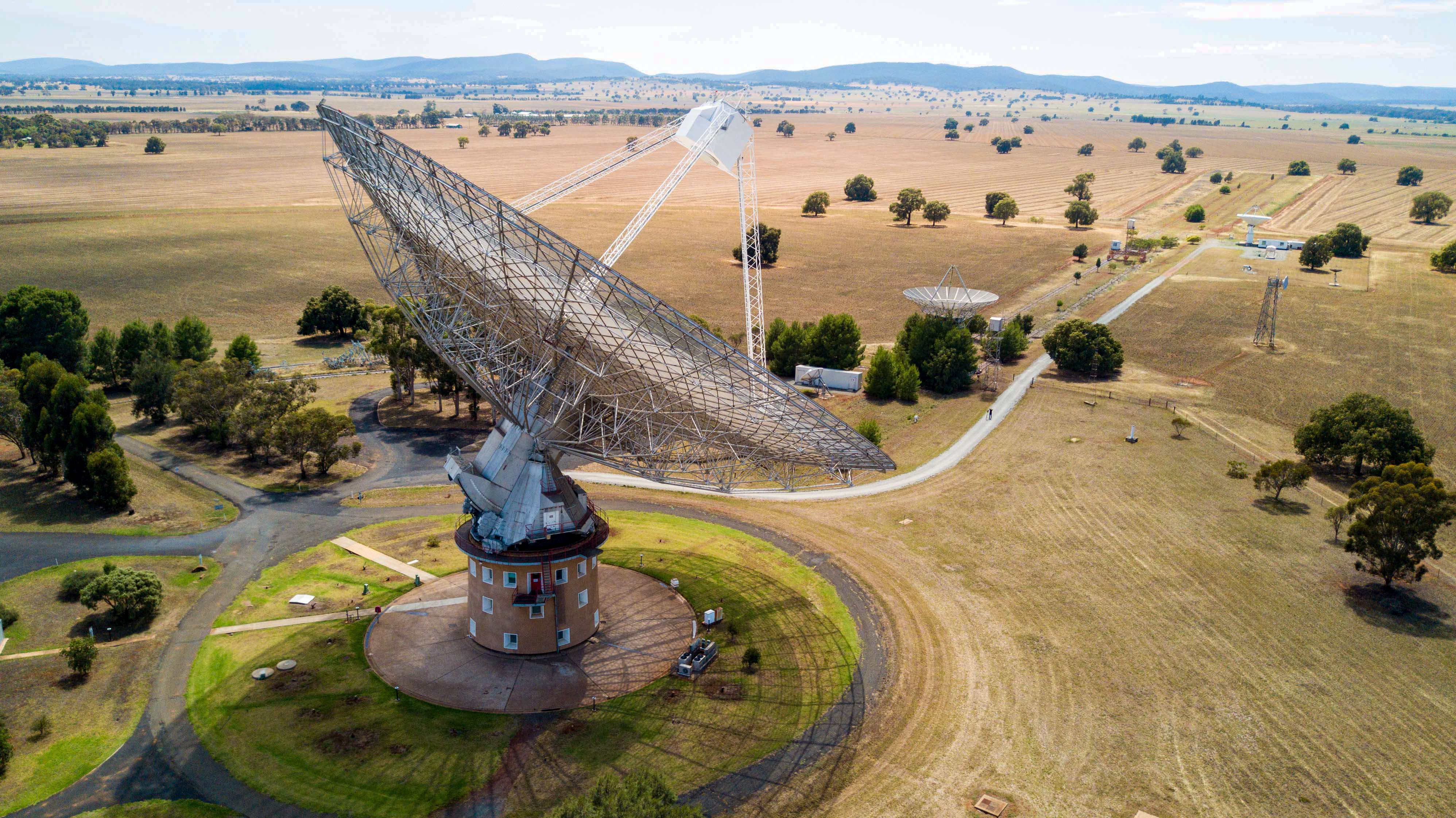 Aerial shot of the Parkes radio telescope, set against golden grassy planes with the telescope raised.