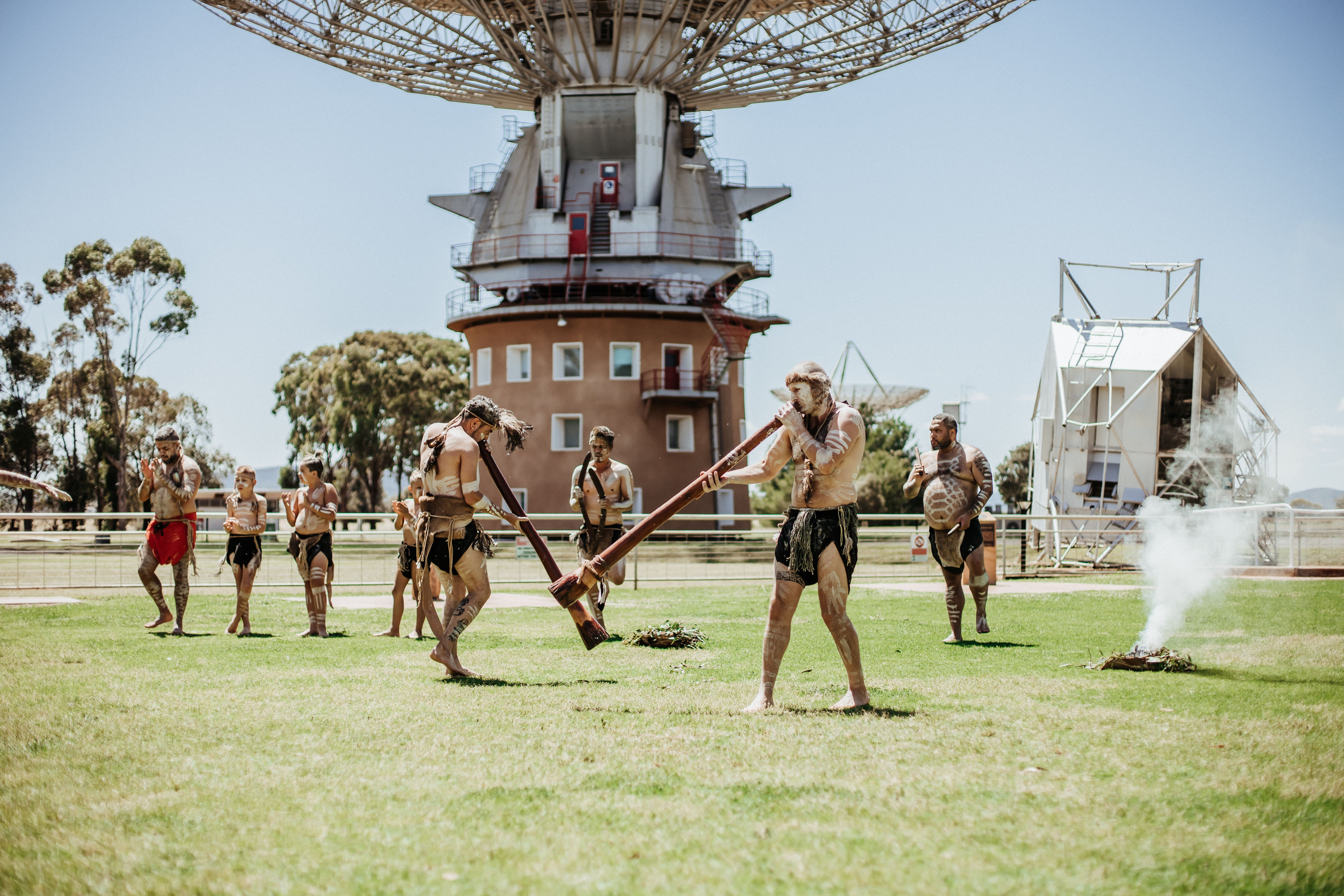 Smoking ceremony conducted by eight Wiradjuri males (3 of which are children) with two males in foreground blowing into digeridoo and a small pile of materials to the right is smoking. In the background is the telescope.