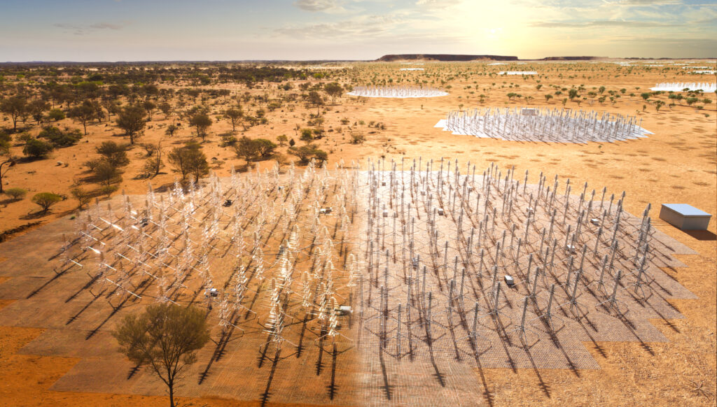 A landscape of red dirt and sparse shrubs is dotted with small antennas that are in circular groups.