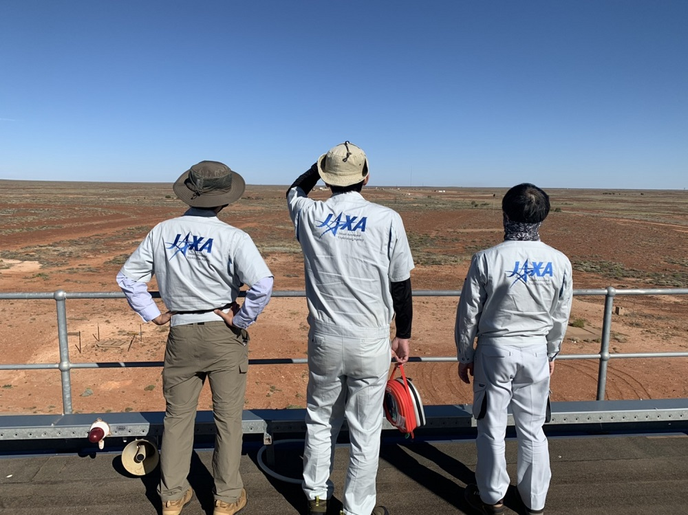 Three JAXA scientists look over the red landscape of the Woomera area in Australia, the retrieval team getting ready to pick up the sample container when it lands on Earth.