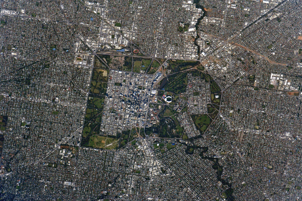 High resolution image of the city of adelaide from space, showing suburbs surrounding a park which encapsulates the city centre.