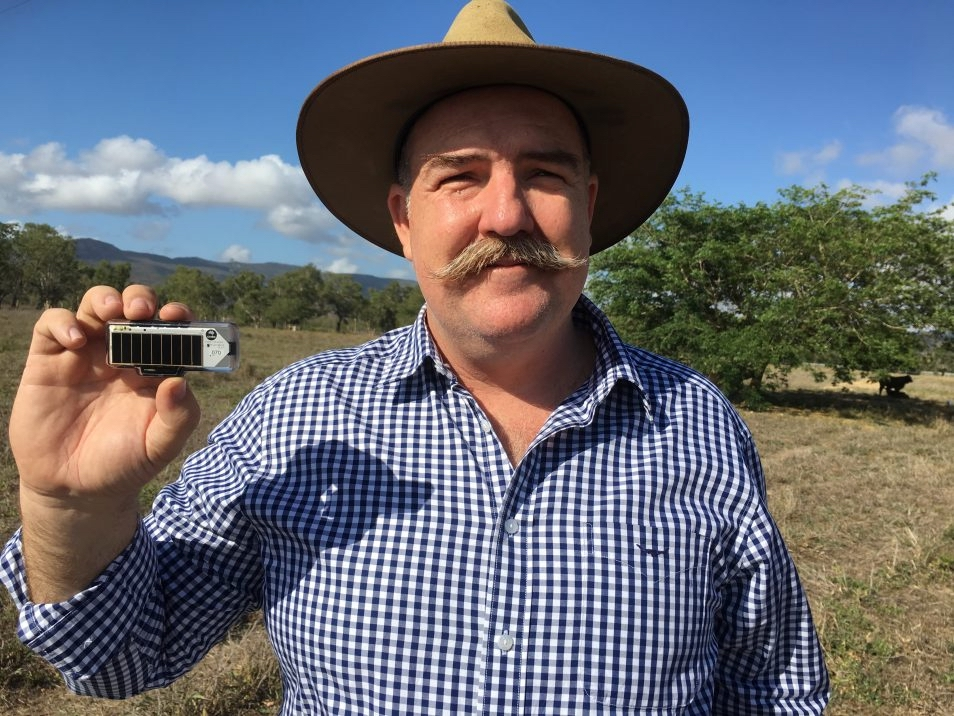 Man on farm holding small device