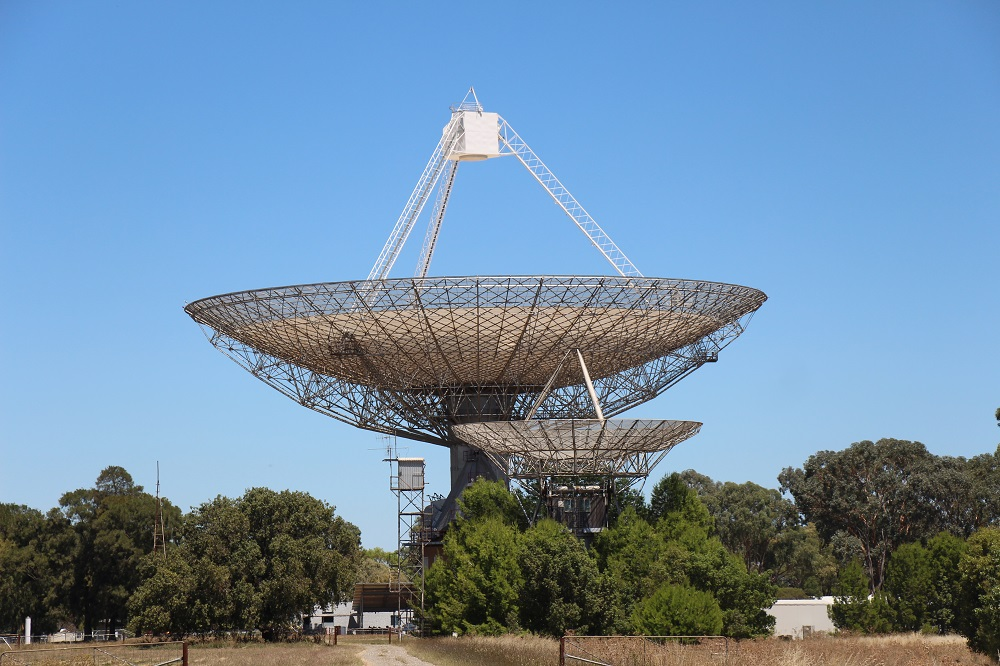 Two dishes in the distance, the larger Parkes Dish and a smaller dish in the foreground. Trees surround both dishes as they are pointing upwards in the blue sky.