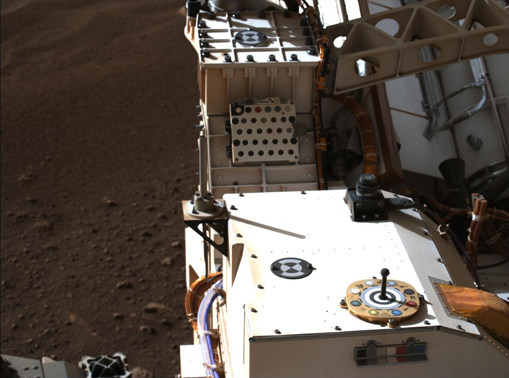 Camera looking down at the hardware of the Perseverance rover with red Martian soil visible